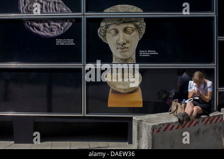 Walbrook Roman archeology Minerva Goddess figure and modern woman using her smartphone by a construction hoarding - Stock Photo