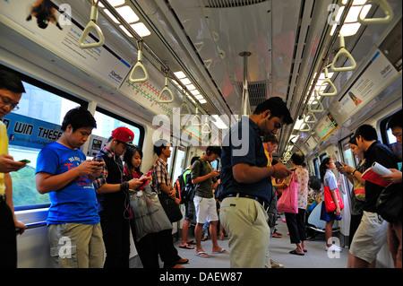 Commuters using technology on MRT Singapore - Stock Photo