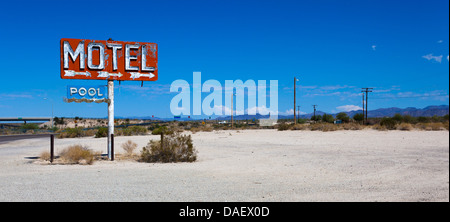 A vintage neon motel sign in the desert with a sky blue background - Stock Photo