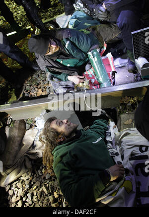 Activist of the environmental group Robin Wood lie chained to the railtracks as police officers try to separate - Stock Photo