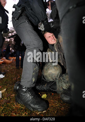Police officers carry away protesters to clear the castor transport route in Gorleben, Germany, 28November 2011. - Stock Photo
