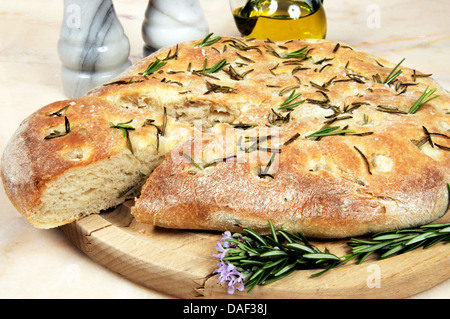 Italian rosemary Focaccia bread on a marble table top. - Stock Photo