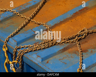 Rusty chains on top of blue also rusty container, Breda, the Netherlands - Stock Photo