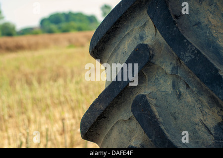 Agricultural tire from tractor standing on the field - Stock Photo