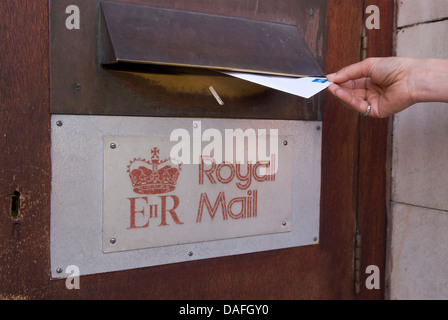 Woman posting a second class letter in main post office, Petersfield, Hampshire, UK. - Stock Photo