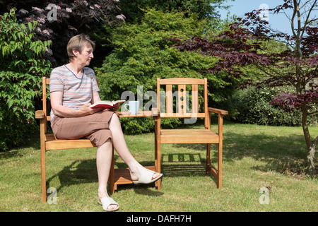 Senior woman widow looking sad and lonely sitting alone beside an empty companion seat in a sunny garden in summer. - Stock Photo