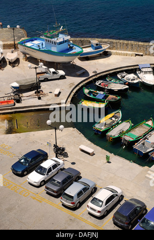 Malta, Parked cars and fishing boats in harbour - Stock Photo
