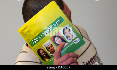 Accused Marcel S. hides his face behind a brochure titled 'We in Saxony'as his trial starts in Dresden, Germany, - Stock Photo