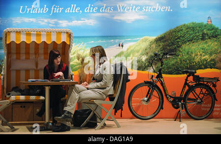 The picture shows two women talking in front of a beach holiday scenery at the visitors booth of Mecklenburg West - Stock Photo