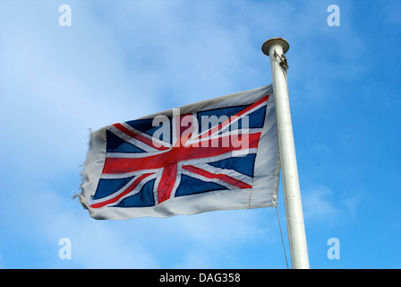 Union Jack flag, blowing in the breeze with blue sky and clouds. - Stock Photo