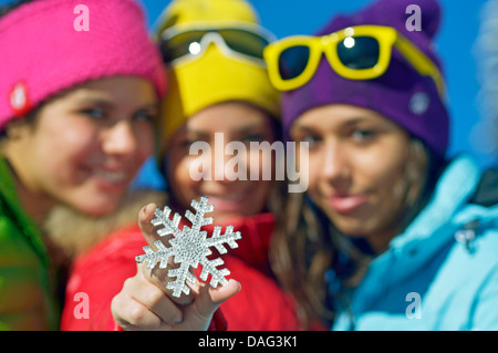 three teenage girls on winter vacation happily presenting a snowflake symbol, France - Stock Photo