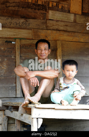 Happy dad carries serious podgy cute son. - Stock Photo