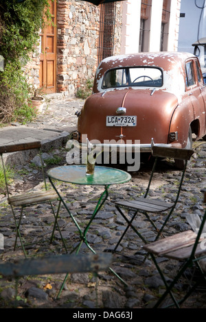 Street scene with cafe tables and vintage Hilman car in Colonia del Sacramento, Uruguay - Stock Photo