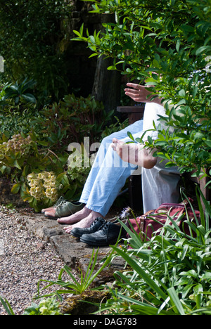 A couple sit and rest their tired feet - Stock Photo