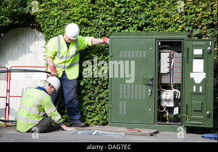 A BT Openreach telecommunications technician working in a manhole at the roadside, Southport, Merseyside, UK - Stock Photo
