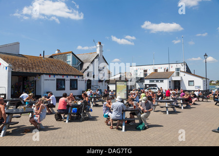 customers sitting around outside tables at haven House Inn Mudeford Quay - Stock Photo