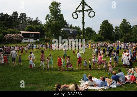 Dancing around Maypole during Midsummer Celebrations in Sweden on small island in Stockholm Archipelago called Trandholmen - Stock Photo