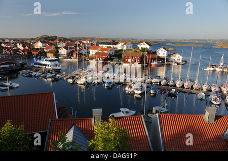 Small harbor filled with boats, yachts, and colorful homes on island of Gullholmen in Bohuslän on West Coast of - Stock Photo