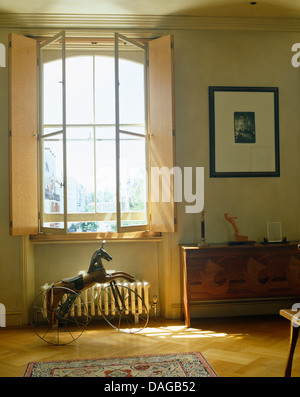 Shutters on tall window above bicycle wheeled metal horse in modern bedroom - Stock Photo