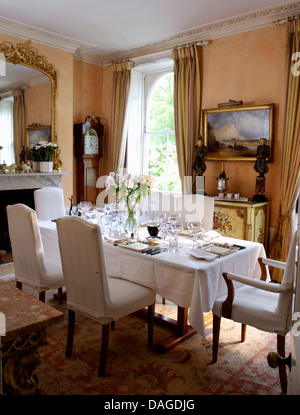 White Loose Covers On Chairs At Table Set For Lunch With Linen Cloth In Pink