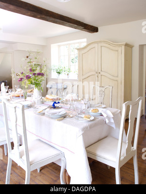 White linen cloth on table set for lunch in white country dining room with painted chairs and cupboard - Stock Photo