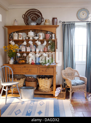 Old pine dresser with collection of pottery and china in French country kitchen with wooden and wicker chairs and - Stock Photo