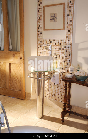 Modern wash basin on chrome pedestal in country bathroom with mosaic tiling and antique side table - Stock Photo