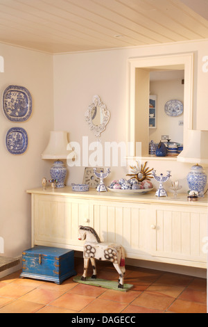 Blue+white pottery on white painted sideboard below hatch in country  dining room with old blue wooden chest and - Stock Photo
