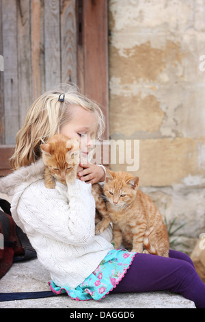 6 year old child holding two ginger cats - Stock Photo