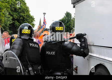 Belfast, Northern Ireland, 12th July 2013 - A PSNI Police officer readies his baton as he is attacked by loyalist - Stock Photo