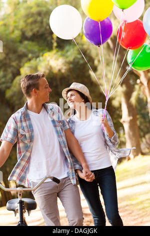 cute teen couple walking at the park holding hands