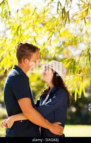 young teenage couple hugging outdoors in forest - Stock Photo