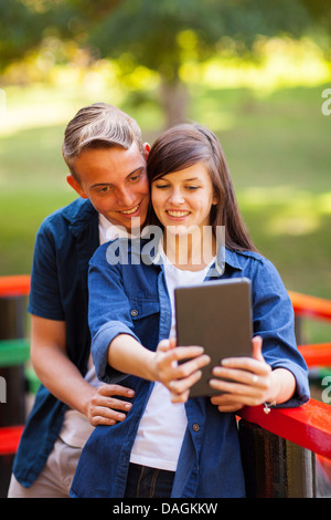cute teenage couple taking self portrait outdoors - Stock Photo