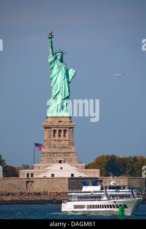 statue of liberty with excursion boat in front seen from the Staten Island Ferry, USA, New York (state), Staten - Stock Photo