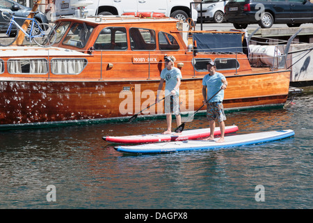Two men stand up paddle boarding on the canal in Nyhavn, Copenhagen, Denmark, - Stock Photo