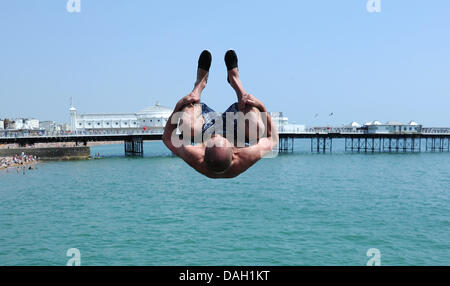 Brighton UK 13 July 2013 - Young men leaping or tombstoning as it is known from a groyne into the sea on Brighton - Stock Photo