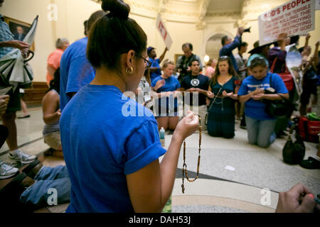 Pro-life supporters kneel in prayer as hundreds of pro-life and pro-choice activists crowd inside the Texas Capital - Stock Photo