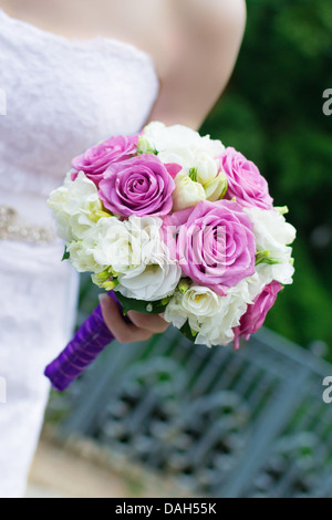 An elegant hand-tied bouquet of flowers in the hand of a bride - Stock Photo