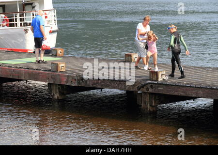 young girl jumping into the water on a hot day. - Stock Photo