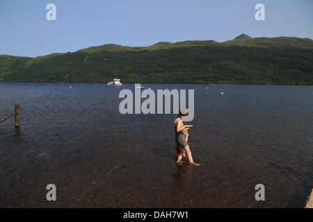 Woman and child paddling in water. Colling down. Loch Lomond, Tarbet, Scotland, UK - Stock Photo