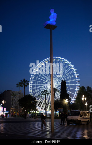 Blue sculpture in foreground, Ferris wheel, big wheel, at night, Nice, France. - Stock Photo