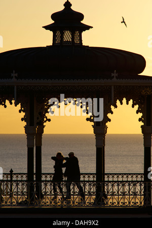 Silhouetted couple dancing on the Victorian bandstand, Brighton seafront. East Sussex, England - Stock Photo