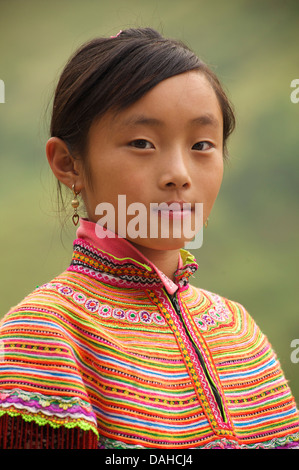 Potrait of a Flower Hmong girl  in her brightly embroidered tribal costume, nr Bac Ha, N Vietnam - Stock Photo