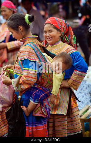 Hmong woman in distinctive tribal costume and carrying child on her back.. Bac Ha market, Lao Cai province, Vietnam. - Stock Photo