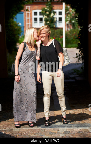 Two young blond girls sharing secrets with eachother - Stock Photo