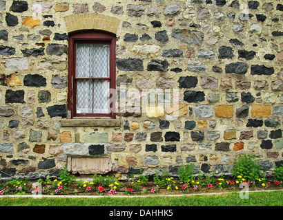 Historic stone wall with brick detail surrounding the window and flower garden lining the path  Grice Historical - Stock Photo
