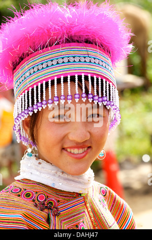 Potrait of a young Flower Hmong woman in distinctive headdress, Coc Ly market, N Vietnam. Model Released - Stock Photo