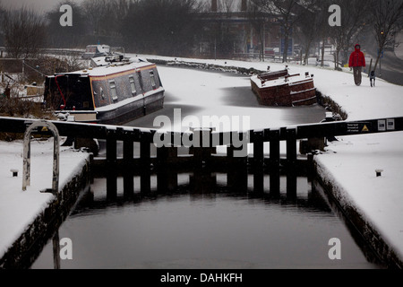 weather Snow on Rochdale canal near Rochdale Road , Slattocks, Middleton . A man walks his dog along the towpath - Stock Photo