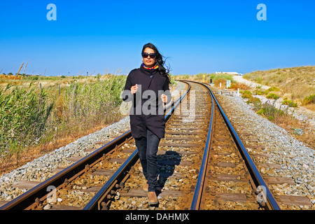 Young beautiful woman running on a railroad track - Stock Photo