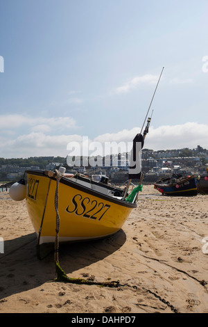 A fishing boat at low tide in St Ives harbour Cornwall - Stock Photo